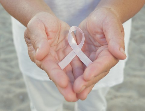 Pair of open human hands close up in front of person with light pink ribbon symbol of surviving breast cancer